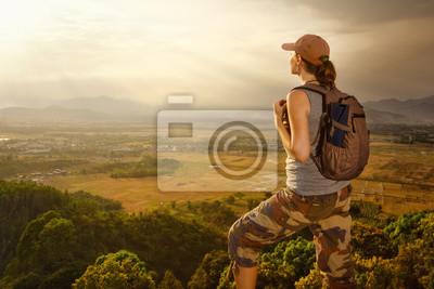 Podróżnik z plecak relaks na szczycie góry i korzystających z widokiem na zachód słońca