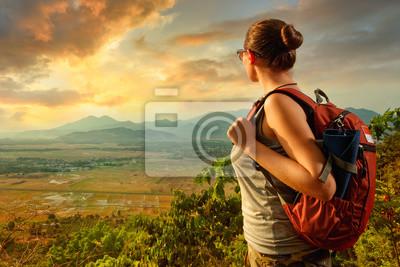 Podróżnik z plecak stojących korzystających widokiem na góry podczas zachodu słońca