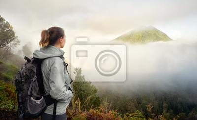 Podróżnik z plecakiem na szczycie góry ciesząc się widokiem na wulkan.