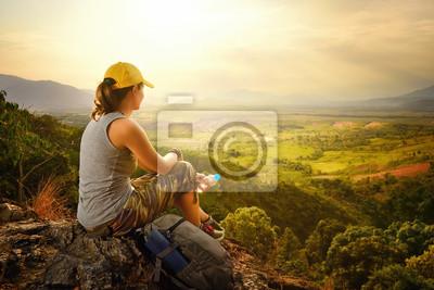 Podróżnik z plecakiem siedzi na szczycie góry i korzystających z widokiem na dolinę
