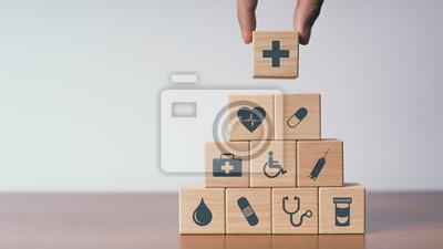 Plakat Pojęcie ubezpieczenia dla twojego zdrowia, Ręka trzymać drewniany blok z ikoną opieki zdrowotnej medycznej