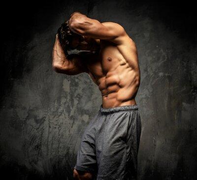 Plakat Półnagi muskularny facet pozowanie w studio.
