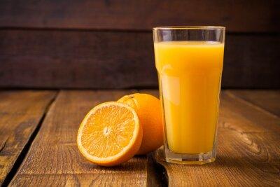 Plakat Pomarańczowe owoce i szkła soku na brązowym tle drewnianych