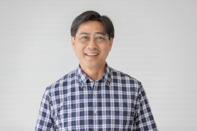 Plakat Portrait close up shot of middle aged asian male model with short black hair wearing blue plaid shirt with stand smiling in front of white background