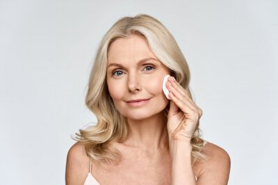 Plakat Portrait isolated on white of beautiful middle age 50 woman doing her everyday routine removing her makeup with cotton pad enjoying anti age healthy perfect products skin. Beauty and care advertising.