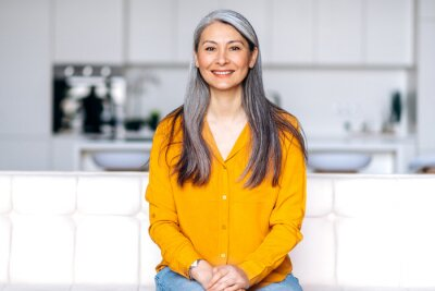 Plakat Portrait of a charming asian senior long gray hair lady wearing casual stylish clothes, sitting on couch at living room, looking directly at the camera with friendly smile