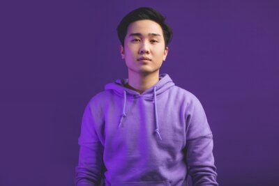 Plakat Portrait of a handsome young Chinese college student, dressed in casual wear. Not emotional guy looking at camera with serious face, isolated at studio against puple wall