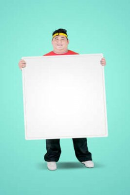 Plakat Portrait of an obese man wearing sportswear while holding a blank whiteboard in the studio