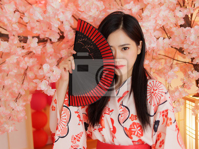 Plakat Portrait of attractive Chinese woman wearing traditional Japanese Kimono, smiling at camera, oriental beauty.