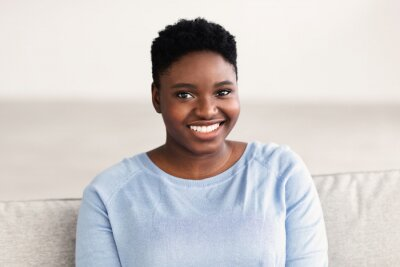 Plakat Portrait of casual young black woman smiling confidently