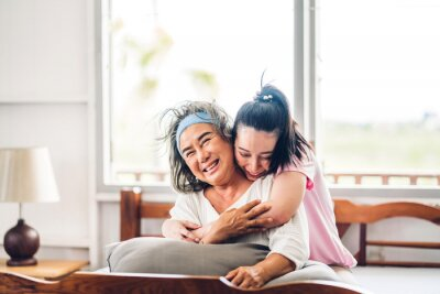 Plakat Portrait of enjoy happy love asian family senior mature mother and young daughter smiling laughing embracing and having fun hug together in moments good time at home