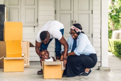 Plakat Portrait of enjoy happy love black family african american father and mother with little african girl smiling sitting in cardboard box at new home unpacking during move and having fun