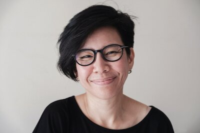 Plakat Portrait of happy and healthy natural looking middle aged Asian woman wearing glasses and smiling at camera