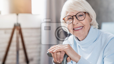 Plakat Portrait of happy mature woman in eyeglasses holding cane while sitting on sofa at home