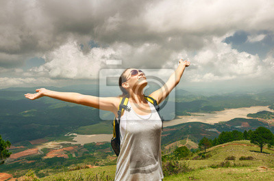 Portrait of happy traveler girl with raised up hands
