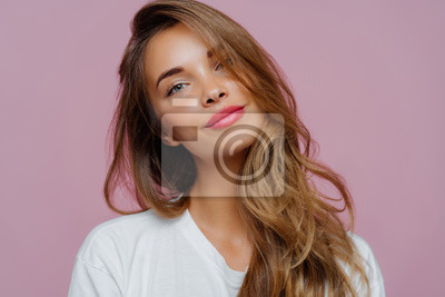 Plakat Portrait of satisfied relaxed young female model tilts head, has makeup, fair hair, dressed in white clothes, poses against purple background, has well cared complexion. People, beauty, face care