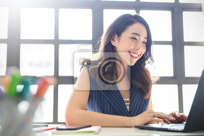 Plakat Portrait of smiling beautiful business asian woman with suit working in office desk using computer with copy space. Business people employee freelance online marketing e-commerce telemarketing concept