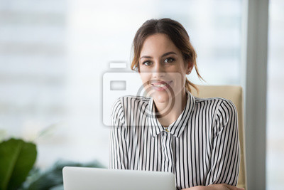 Plakat Portrait of smiling beautiful millennial businesswoman or CEO looking at camera, happy female boss posing making headshot picture for company photoshoot, confident successful woman at work