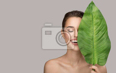 Plakat Portrait of woman and green leaf. Organic beauty. Gray background.