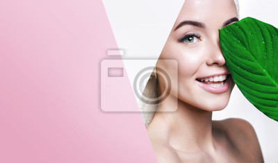 Plakat Portrait of young beautiful woman with healthy glow perfect smooth skin holds green tropical leaf, look into the hole of colored pink paper. Model with natural nude make up. Fashion, beauty, skincare.