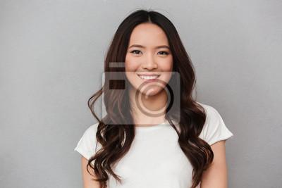 Plakat Portret azjatykcia urocza kobieta z ciemnym kędzierzawym włosy pozuje z dobrym uśmiechem, odosobniony nadmierny szary tło