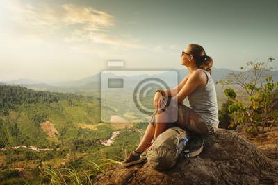 Portret kobiety z plecakiem siedzi na szczycie góry ciesząc się widok na zachód słońca i doliny