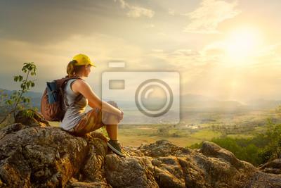 Portret kobiety z plecakiem siedzi na szczycie góry ciesząc się widokiem na dolinę