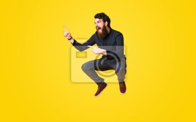 Plakat Portret krzyczy brodaty mężczyzna i skacze nad żółtym tłem i wskazuje daleko od