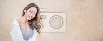 Plakat Portret młoda piękna azjatykcia kobieta siedzi i relaksuje nad rocznik ścianą. Uśmiecha się szczęśliwej azjatykciej dziewczyny patrzeć. Stylu życia piękna dziewczyny następnego drzwi pojęcia sztandaru
