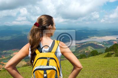 Portret młodej kobiety turystą z plecak stojących na szczycie