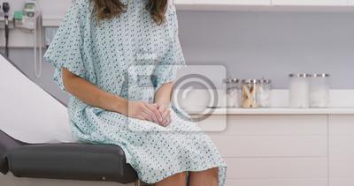 Plakat Portret młody żeński pacjent siedzi na kliniki krześle jest ubranym szpitalną suknię. Zamknij widok wieloetnicznego kobieta siedzi na fotelu medycznym w klinice szpitalnej
