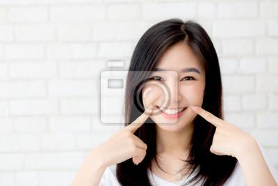 Plakat Portret piękny młody azjatykci kobiety szczęścia pozyci palca dotyka policzek na popielatym cementowym tekstury grunge ściany ceglanym tle, bizneswoman jest uśmiechnięty na betonu, ludzi biznesu pojęc