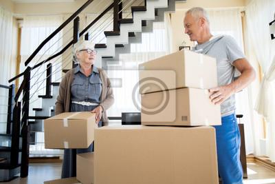 Plakat Portret szczęśliwa starsza para pakuje kartony podczas gdy ruszający się nowy dom