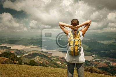 Portret szczęśliwy podróżnika z plecakiem stoi na szczycie,