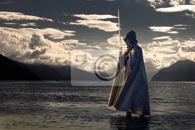 Plakat Portret zabójcy w białym kostiumie z mieczem na morzu. Pozuje blisko wody podczas zachodu słońca, miękkie światło.