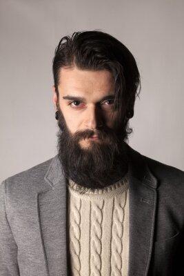 Plakat poważny młody człowiek z długą brodą stwarzających w studio