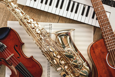 Plakat Power of music. Top view of musical instruments set: synthesizer, guitar, saxophone and violin lying on the sheets for music notes over wooden floor