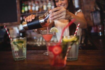 Plakat Pretty barman nalewania koktajl napoju w szkle