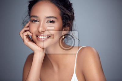 Plakat pretty girl smiling into the camera, beautiful woman with smile, happy girl on grey background leaning on her arm, nice girl laughing