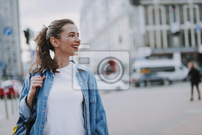 Plakat Pretty smiling young female walking around city