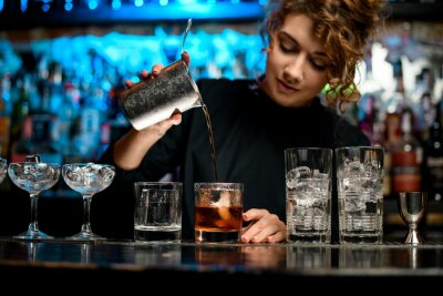 Plakat Pretty woman barman preparing cocktail and pouring it into glass.