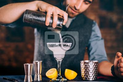 Plakat Profesjonalny barman leje margarita koktajl z sitkiem i narzędzia koktajlowe