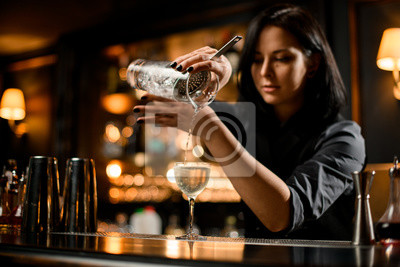 Plakat Professional bartender girl pouring a trasparent alcoholic drink from the measuring cup to the glass through the strainer filter