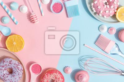 Plakat Przybory kuchenne i narzędzia, ciasta i słodycze na różowym i niebieskim tle. Widok z góry. Skopiuj miejsce