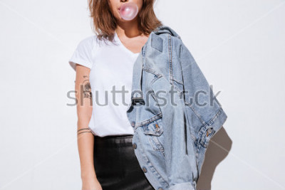Plakat Przycięta fotografia młoda dama ubierająca w cajg kurtki pozyci odizolowywającej nad białym tłem podczas gdy dmuchający bąbel z gumą do żucia.