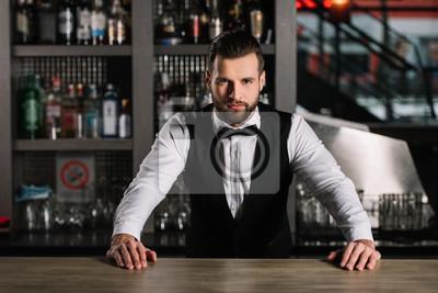 Plakat przystojny barman opierając się na kontuarze i patrząc na kamery
