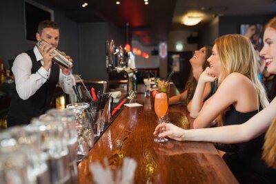 Plakat Przystojny barman przygotowywania koktajli dla pięknych kobiet