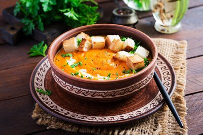 Pumpkin soup in a bowl served with croutons and parsley. Vegan diet soup. Vegetarian food.