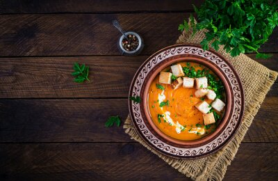 Pumpkin soup in a bowl served with croutons and parsley. Vegan diet soup. Vegetarian food. Top view, overhead