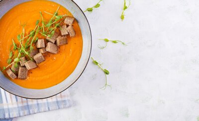 Pumpkin soup in a bowl served with croutons and pea sprouts. Vegan diet soup. Vegetarian food. Top view, overhead